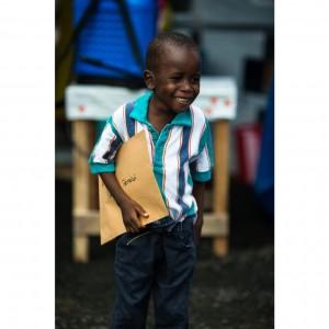 Patrick Poopel, de seis años, con el documento que certifica que ha superado el ébola. / MORGANA WINGARD